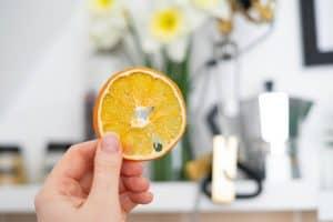 person holding orange fruit in shallow focus lens
