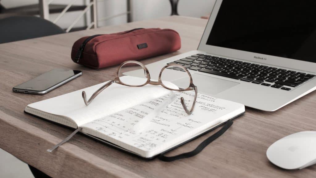 eyeglasses on book beside laptop at college