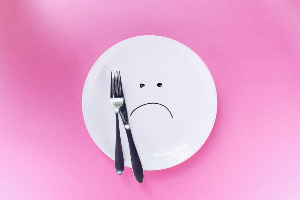 silver fork and knife on plate with frown face